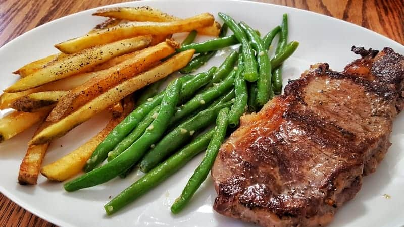 rib eye with fries and garlic butter green beans