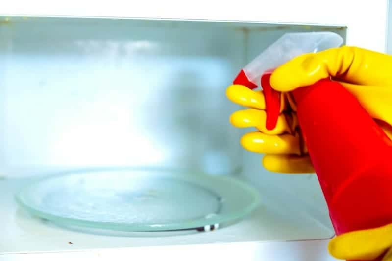 Woman hands in rubber gloves washing microwave